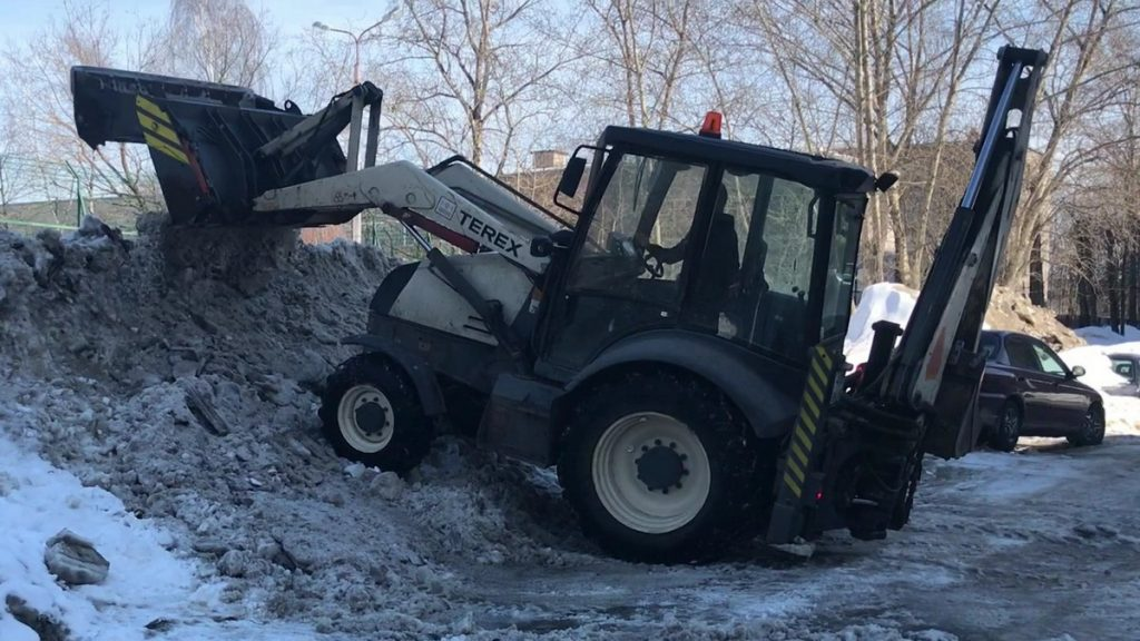 Осуществляется уборка снега трактором во дворе, Череповец